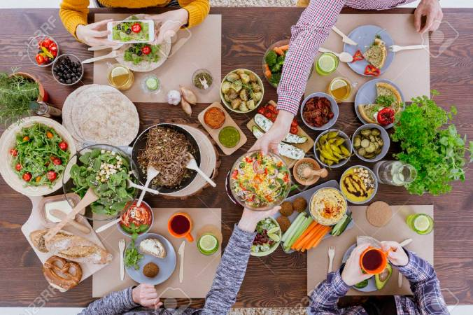 68548694-friends-having-vegetarian-feast-sitting-at-rustic-table